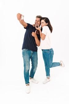 Per tutta la lunghezza di una coppia allegra e attraente che indossa un abito casual in piedi isolato su un muro bianco, facendo un selfie