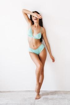 Per tutta la lunghezza di una bella ragazza bruna allegra che indossa un bikini in piedi isolato su un muro bianco