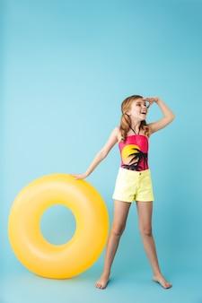 Per tutta la lunghezza di una bambina allegra che indossa il costume da bagno in piedi isolata sul muro blu