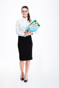 Per tutta la lunghezza di una giovane donna d'affari allegra in piedi e in possesso di cartelle su un muro bianco