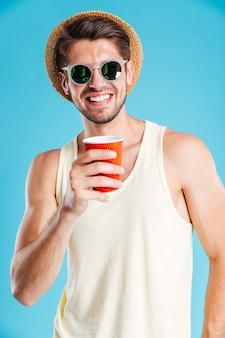Per tutta la lunghezza del giovane allegro con cappello e occhiali da sole in piedi e bevendo caffè sul muro blu