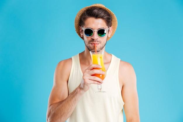 Per tutta la lunghezza del giovane allegro in piedi e bevendo un bicchiere di succo d'arancia sul muro blu
