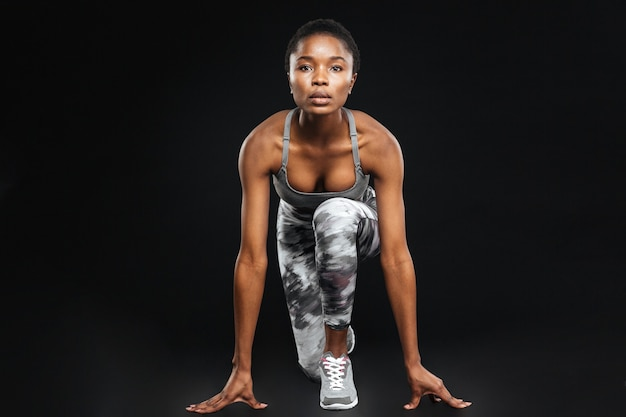 Integrale di bella giovane sportiva concentrata sopra la parete nera