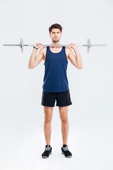 Per tutta la lunghezza dell'atleta concentrato del giovane che si allena con il bilanciere su sfondo bianco