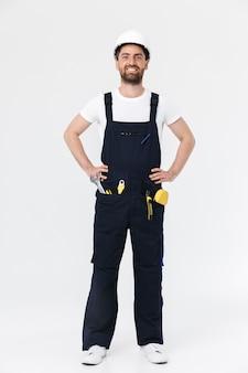 Per tutta la lunghezza di un costruttore barbuto fiducioso che indossa tuta e elmetto protettivo in piedi isolato su un muro bianco, braccia conserte