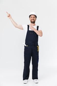 Integrale di un uomo fiducioso costruttore barbuto che indossa tuta e elmetto protettivo in piedi isolato sul muro bianco, puntando il dito sullo spazio della copia