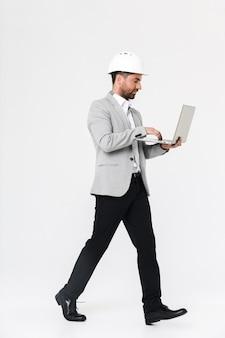 Per tutta la lunghezza di un costruttore di uomini barbuti fiducioso che indossa tuta e elmetto protettivo in piedi isolato su un muro bianco, utilizzando un computer portatile