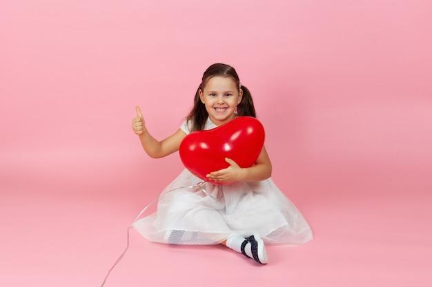 Bambino contento a figura intera in un abito bianco tiene un palloncino rosso a forma di cuore e dà un pollice in alto