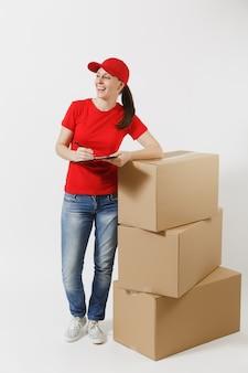 Integrale della donna di consegna in berretto rosso, maglietta isolata su fondo bianco. corriere femminile che tiene appunti con documenti cartacei, foglio vuoto vuoto su scatole di cartone vuote. ricezione pacco.