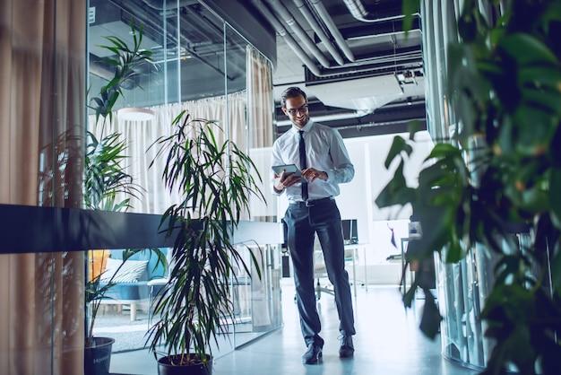 Integrale dell'uomo d'affari barbuto caucasico sorridente elegante in camicia e cravatta e con gli occhiali che camminano sul corridoio e facendo uso della compressa.