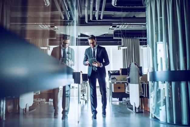 Integrale dell'uomo d'affari barbuto caucasico sorridente elegante in vestito e con gli occhiali che camminano sul corridoio e facendo uso della compressa.