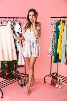 Tutta la lunghezza della donna eccitata in abito in piedi vicino al guardaroba con i vestiti e scegliendo cosa indossare isolato sul rosa