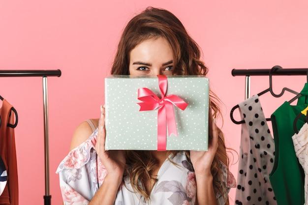 Tutta la lunghezza della moda donna che indossa un abito in piedi in negozio vicino a stendibiancheria con acquisti isolati in rosa