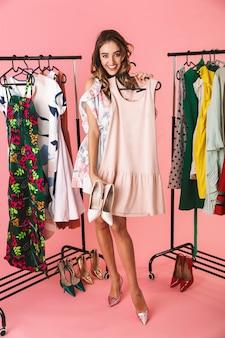 Integrale del cliente femminile in vestito che sta vicino al guardaroba con i vestiti e che sceglie cosa indossare isolato sul rosa