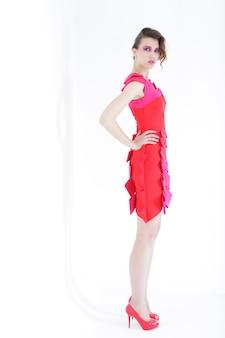Giovane modella femminile integrale che indossa la posa rosa del vestito