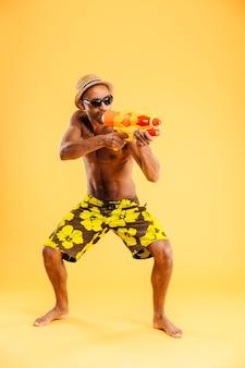 Integrale del giovane afro divertente in costume da bagno che spara con la pistola ad acqua sopra la parete arancione