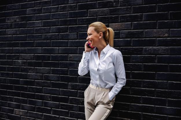Integrale della donna di affari alla moda bionda splendida che si appoggia sul muro e che ha telefonata.