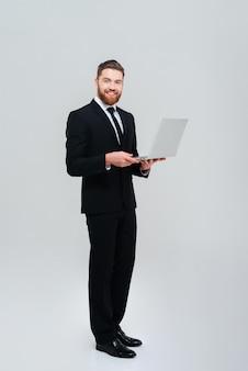 Uomo d'affari barbuto bello a figura intera in abito nero con laptop