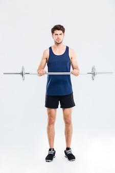 Per tutta la lunghezza del bel giovane sportivo che fa esercizi e si allena con il bilanciere su sfondo bianco