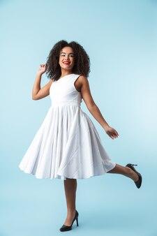 Integrale di un vestito da portare della donna africana felice che celebra isolato, posa
