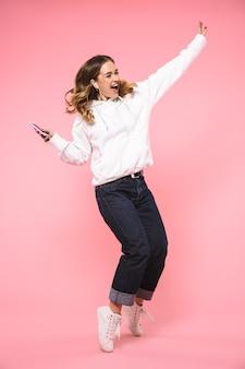 Donna bionda felice integrale che indossa in abiti casual ascoltando musica e ballando sul muro rosa