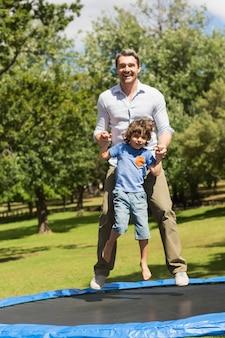 Integrale di un ragazzo felice e padre saltando in alto sul trampolino nel parco