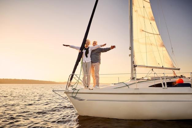 Tutta la lunghezza di una coppia anziana felice che allunga le mani contro il cielo godendosi un tramonto incredibile e