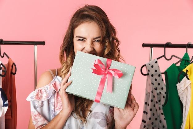 Integrale del vestito da portare della donna felice che sta nel deposito vicino alla cremagliera dei vestiti con le caselle attuali isolate sul colore rosa
