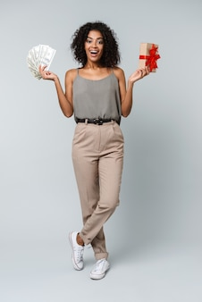 Integrale di una giovane donna africana felice vestita con indifferenza in piedi isolato, in possesso di un contenitore di regalo, mostrando le banconote dei soldi