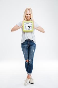 Integrale della giovane donna felice che sta e che tiene l'orologio isolato su un muro bianco