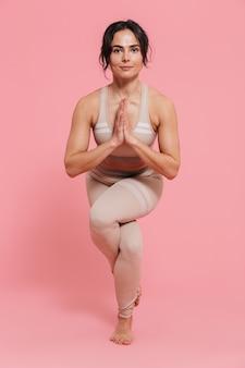 Per tutta la lunghezza di una giovane donna in buona salute che indossa abbigliamento sportivo facendo esercizi di stretching isolati su una parete rosa