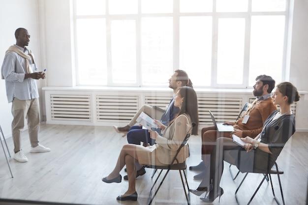 Vista dall'alto a tutta lunghezza delle persone che ascoltano il coach aziendale mentre sono seduti su sedie tra il pubblico a conferenze o seminari, riflesso lente, spazio copia