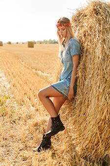 Immagine integrale della donna adorabile 20s che sta vicino al grande pagliaio nel campo dorato e sigaretta fumante durante la giornata di sole
