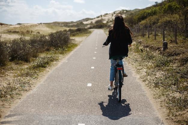 Immagine a figura intera. vista posteriore di una giovane ragazza cammina single in bicicletta sulla strada in tempo di giorno pieno di sole.