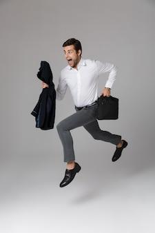 Immagine a figura intera di uomo d'affari di 30 anni in tailleur in esecuzione con borsa e giacca in mano, isolato sopra il muro grigio