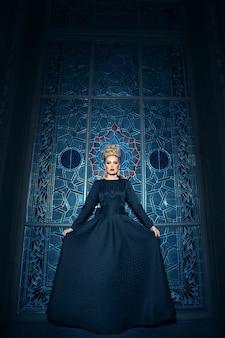 Immagine a figura intera di una grande giovane modella bionda, vestita con un lungo abito nero, con acconciatura elegante, corona e orecchini.