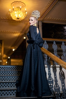 Immagine a figura intera di una grande giovane donna bionda, vestita con un lungo abito nero, con acconciatura elegante, grande corona e orecchini.