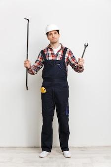 Immagine a figura intera del costruttore maschio pensieroso nel casco protettivo che sceglie tra piede di porco e chiave mentre osserva in su sopra il muro grigio