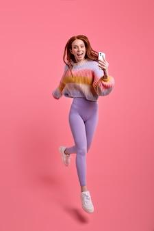 Immagine a tutta lunghezza della donna rossa scioccata in abiti casual che salta e si affretta a scattare foto, su smartphone su sfondo rosa. emozioni umane, concetto di stile di vita delle persone