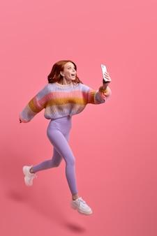 Immagine a tutta lunghezza della donna scioccata in abiti casual che salta e si affretta a scattare foto, su smartphone su sfondo rosa. emozioni umane, concetto di stile di vita delle persone