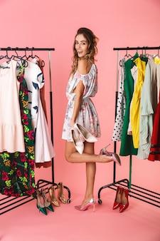 Integrale della donna allegra in vestito che sta vicino al guardaroba con i vestiti e che sceglie cosa indossare isolato sul colore rosa
