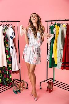 Tutta la lunghezza della donna gioiosa in abito in piedi vicino al guardaroba con i vestiti e scegliendo cosa indossare isolato sul rosa