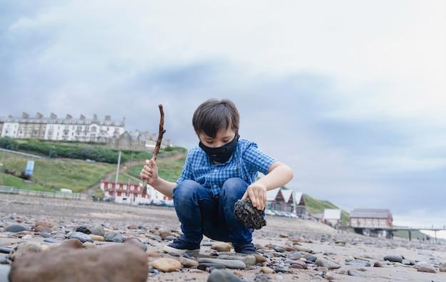 Bambino a figura intera che indossa una maschera protettiva per l'inquinamento o il virus