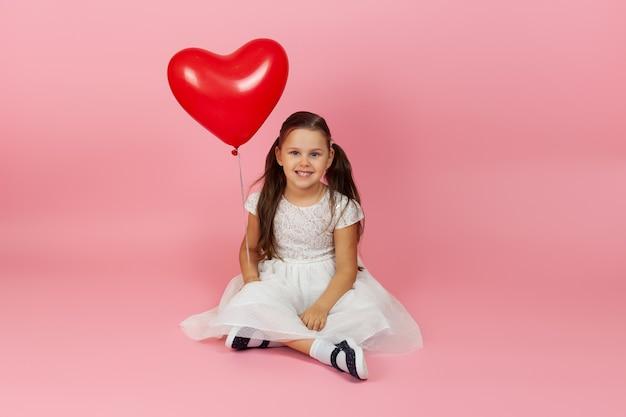 Bella bella ragazza a figura intera in abito bianco tiene un palloncino rosso a forma di cuore e si siede a gambe incrociate