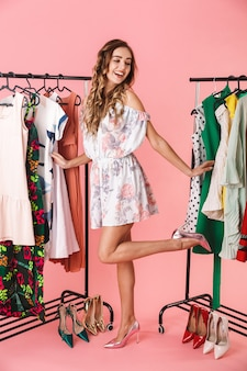 Integrale della bella donna in abito in piedi vicino al guardaroba con vestiti e scegliendo cosa indossare isolato sul rosa