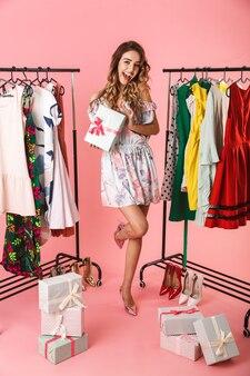 Integrale del vestito da portare della donna adorabile che si leva in piedi nel deposito vicino all'appendiabiti con gli acquisti isolati sul colore rosa