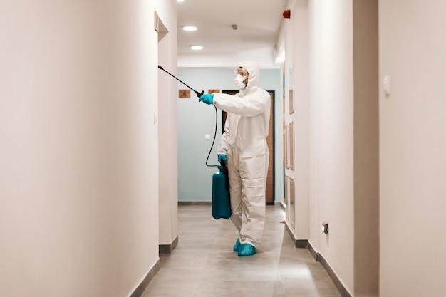 Integrale dell'uomo in vestito sterile che disinfetta la sala dell'edificio. protezione dal concetto corona.