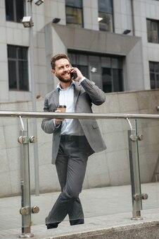 Uomo maturo a figura intera in abito grigio che guarda da parte con un sorriso, stando in piedi e bevendo caffè da asporto davanti al moderno centro business durante la chiamata di lavoro