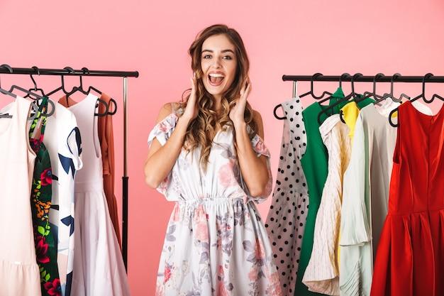 Integrale della donna moderna in abito in piedi vicino al guardaroba con vestiti e scegliendo cosa indossare isolato sul rosa
