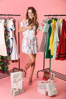 Integrale del vestito da portare della donna moderna che sta nel deposito vicino allo stendibiancheria con le caselle presenti isolate sul colore rosa